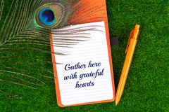 Gather here with grateful hearts. Text in notebook with peacock feather , pen and heart shape on grass stock images