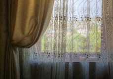 Gathered curtains and blinds on the window of the room Stock Photography