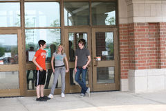 Gathering. Teen guys and girl outside front of school royalty free stock images