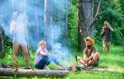 Gathering for great picnic. Company having fun while roasting sausages on sticks. Friends meeting at meadow to hang out. And prepare roasted sausages snacks royalty free stock image