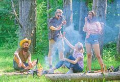 Gathering for great picnic. Company having fun while roasting sausages on sticks. Friends meeting near bonfire to hang royalty free stock image