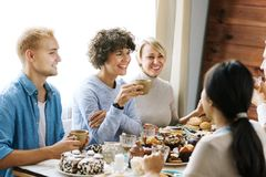 Talk by festive table. Gathering of happy young friends by cup of tea or festive dinner Royalty Free Stock Images