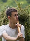 Gathering hay. Young man with glasses, gathering hay looking proudly stock photo