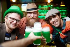 Gathering in pub. Happy friends toasting with glasses of foaming beer while gathering in pub Royalty Free Stock Photography