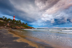 Gathering storm on beach and lighthouse. Gathering storm on beach and Kovalam (Vizhinjam) lighthouse on stormy sunset. Kerala, India Royalty Free Stock Photos