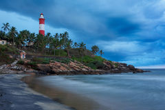Gathering storm on beach and lighthouse on sunset Stock Images