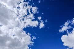 High-altitude clouds seen during the summer, against a blue background, prior to a storm. Gathering storm clouds can be seen in this view of a summer sky. The Royalty Free Stock Image