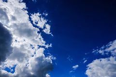 High-altitude clouds seen during the summer, against a blue background, prior to a storm. Gathering storm clouds can be seen in this view of a summer sky. The Royalty Free Stock Photo