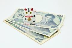 Gato afortunado en billetes de banco de los yenes japoneses Fotos de archivo