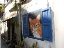 Gato alaranjado que olha para fora a janela Arte Kuala Terengganu da rua, Malásia fotografia de stock royalty free