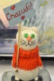 Gato blanco del juguete en un suéter anaranjado Foto de archivo