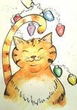 Gato con las luces de la Navidad Foto de archivo libre de regalías