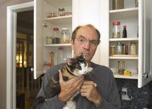 Gato da terra arrendada do homem na cozinha Fotografia de Stock
