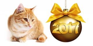 gato del jengibre de 2017 textos con el arco de oro de la cinta de la pizca de la bola de la Navidad Imágenes de archivo libres de regalías