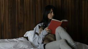 Gato do abraço da mulher que lê um livro filme