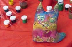 Gato do brinquedo de pano pintado com cores diferentes Gato macio do brinquedo em um fundo vermelho imagens de stock