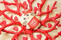 Gato dulce del pan de jengibre pequeño en florero de la forma del coral rojo Fotos de archivo libres de regalías