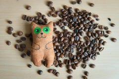 Gato lindo que se sienta en el centro de los granos de café Foto de archivo libre de regalías