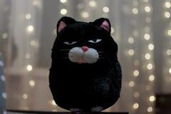 Gato macio do brinquedo com uma expressão irritada em sua cara no fundo da festão borrada imagens de stock royalty free
