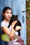 Gato negro del ingenio bonito adolescente de la muchacha Imagen de archivo