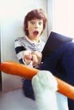 Gato que roba la salchicha del muchacho de la lectura Imagen de archivo