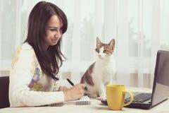 Gato que se sienta cerca de la muchacha Foto de archivo libre de regalías