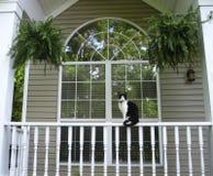 Gato que se sienta en Front Porch Rail del hogar Imagenes de archivo