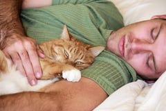 Gato y hombre que ponen en una cama Foto de archivo libre de regalías