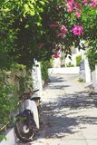 Gator av den Neorio staden i den Poros ön, Grekland; Moped som parkeras i smal gata arkivbild