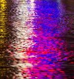 Gator efter regn med reflexioner av ljus på den våta körbanan Arkivfoto