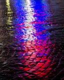 Gator efter regn med reflexioner av ljus på den våta körbanan Arkivbild