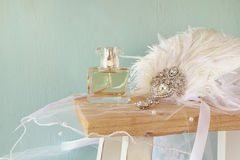 Gatsby style diamond head decoration with feathers. Image of gatsby style diamond head decoration with feathers next to perfume bottle on old table royalty free stock photography
