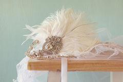 Gatsby style diamond head decoration with feathers. Image of gatsby style diamond head decoration with feathers on old table royalty free stock images