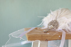 Gatsby style diamond head decoration with feathers. Image of gatsby style diamond head decoration with feathers on old table royalty free stock photo