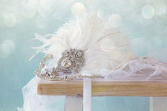 Gatsby style diamond head decoration with feathers. Image of gatsby style diamond head decoration with feathers on old table. Glitter overlay stock image