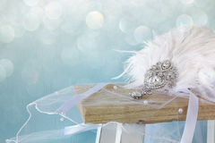 Gatsby style diamond head decoration with feathers. Image of gatsby style diamond head decoration with feathers on old table. Glitter overlay stock photography
