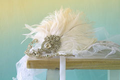 Gatsby style diamond head decoration with feathers. Image of gatsby style diamond head decoration with feathers on old table. vintage filtered and toned stock photos