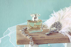Gatsby style head decoration with feathers next to perfume Stock Photo