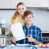 Gatten, die Dokumente unterzeichnen und an der Küche lächeln Stockfotografie