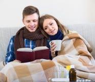 Gatten, die Kamin zusammen, sitzend mit Buch und Tee haben Lizenzfreie Stockbilder