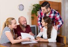 Gatten, die mit Dokumenten sitzen und Freunde um Rat bitten Lizenzfreies Stockbild