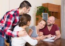 Gatten, die mit Dokumenten sitzen und Freunde um Rat bitten Lizenzfreie Stockfotos