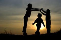 Gatter - Schattenbild der Kinder durch Spiel im Sonnenuntergang Lizenzfreies Stockfoto