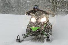 Gatto delle nevi all'alta velocità mentre sta nevicando nell'abetaia Fotografie Stock