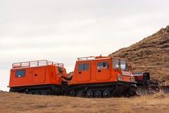 Gatto delle nevi arancio con il secondo vagone Un altro veicolo con lo spazzaneve fotografia stock