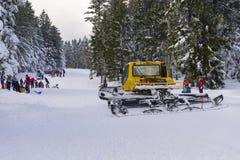 Gatto delle nevi che prepara pendio per i bambini con sledding dei genitori Immagini Stock Libere da Diritti