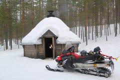 Gatto delle nevi davanti a Kota finlandese in un paesaggio innevato Fotografie Stock