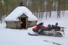 Gatto delle nevi davanti a Kota finlandese in un paesaggio innevato Immagine Stock Libera da Diritti