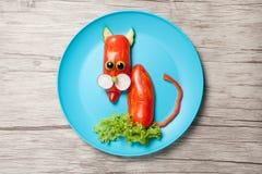Gatto divertente fatto di pepe sul piatto e sul fondo di legno Fotografia Stock
