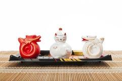 Gatto e drago di ceramica sul cassetto di plastica isolato sopra fotografia stock
